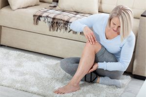 The woman is holding her leg due to muscle pain.